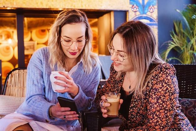 Pareja de mujeres tomando café en una terraza en vacaciones de primavera y llamando a un amigo con teléfono inteligente.