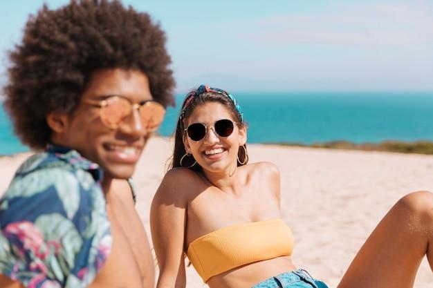 Pareja multicultural descansando en la playa