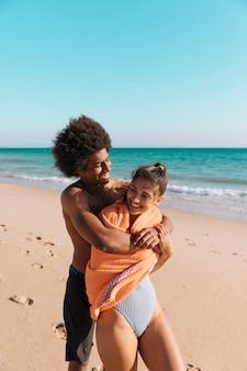 Pareja multicultural divirtiéndose en la playa