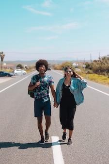 Pareja multiétnica caminando en la carretera