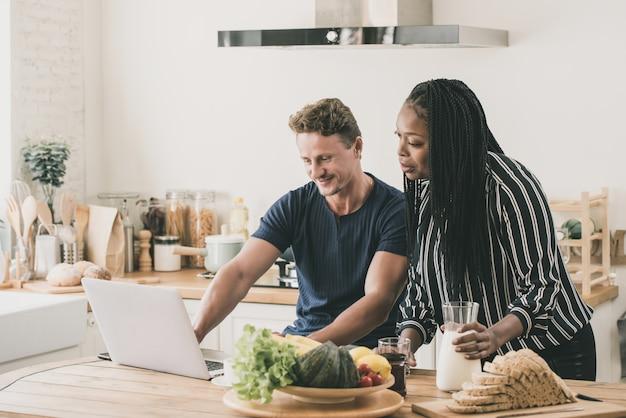 Pareja multiétnica desayunando mientras trabaja en casa