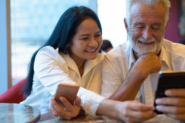 Pareja multiétnica madura feliz y enamorada mientras explora la ciudad de bangkok