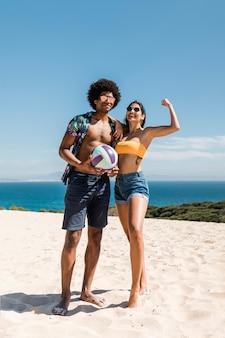 Pareja multirracial con bola posando en la playa