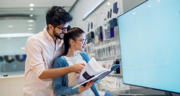Pareja multirracial de compras en la tienda electrónica buscando en un catálogo de productos. servicio de atención al cliente.