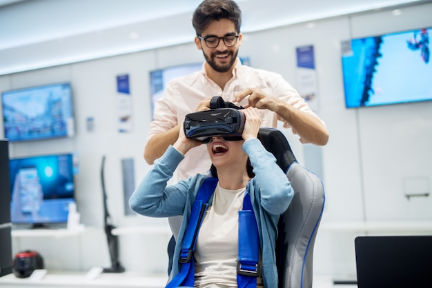 Pareja multirracial divirtiéndose con gafas de realidad virtual mientras niña sentada en la silla en la tienda de tecnología. servicio de atención al cliente. tiempo de compras.