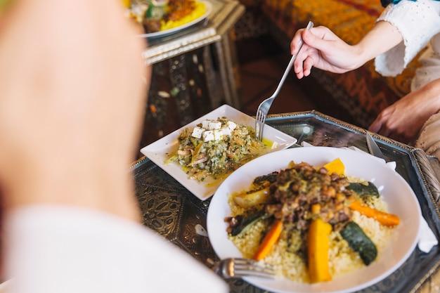 Pareja musulmana comiendo plato en restaurante