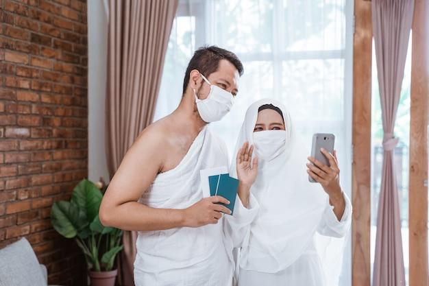 Pareja musulmana haciendo una llamada telefónica mientras umrah y hajj