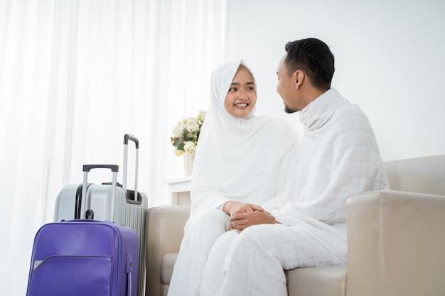 Pareja musulmana sentada vistiendo ropas blancas tradicionales antes de la umrah