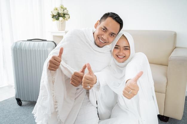 Pareja musulmana sentarse vistiendo blanco tradicional con las manos pulgar arriba