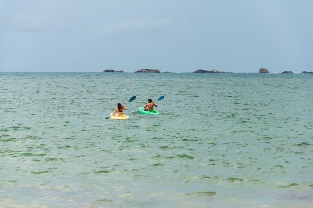 Una pareja nada en un kayak o canoa en el mar o el océano. concepto de kayak o piragüismo con personas. espacio para texto