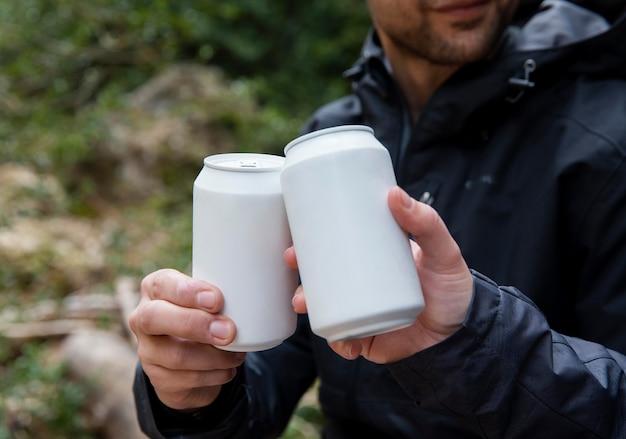 Pareja en la naturaleza bebiendo bebidas de cerca
