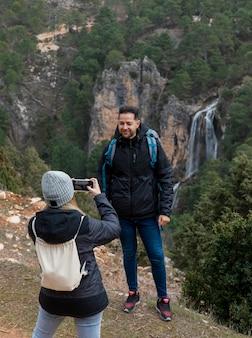 Pareja en la naturaleza tomando fotos con el móvil