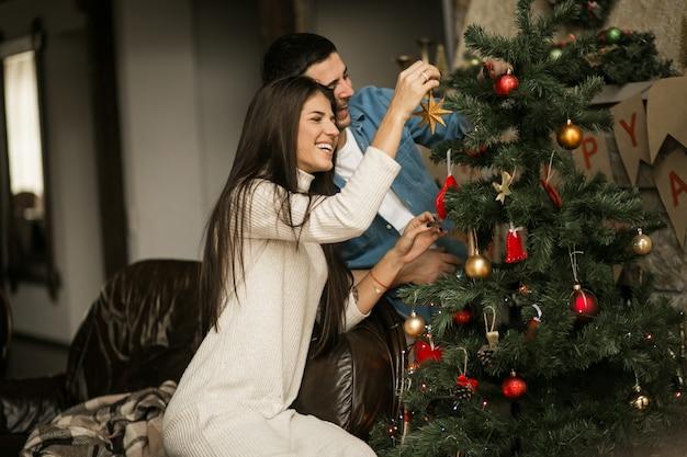 Pareja en navidad con el árbol