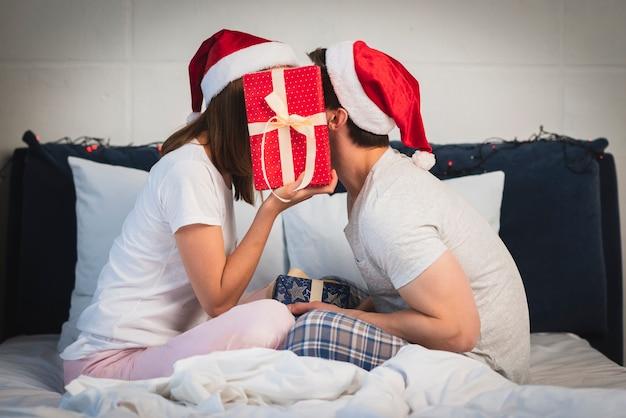 Pareja de navidad escondiéndose detrás de regalo