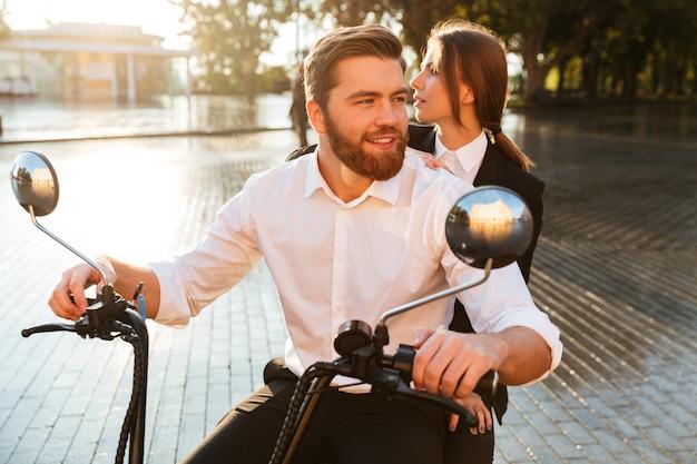 Pareja de negocios despreocupada monta en moto moderna en el parque