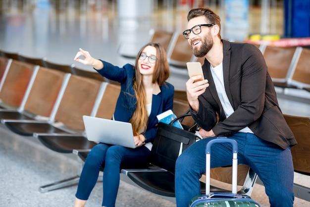 Pareja de negocios elegante sentado con laptop, teléfono y maleta en la sala de espera en el aeropuerto. concepto de viajes de negocios