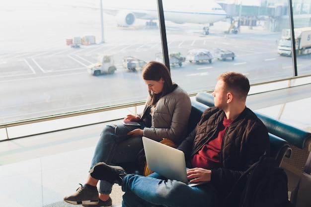 Pareja de negocios elegante trabajando con ordenador portátil y teléfono sentado en la sala de espera en el aeropuerto. concepto de viaje de negocios.