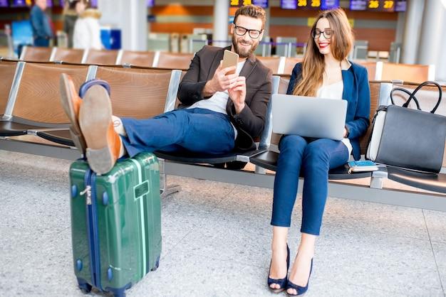 Pareja de negocios elegante trabajando con ordenador portátil y teléfono sentado en la sala de espera en el aeropuerto. concepto de viajes de negocios