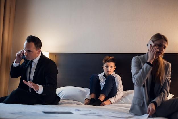 Una pareja de negocios en una habitación de hotel con su hijo