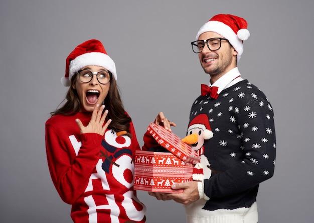 Pareja nerd abriendo regalo de navidad