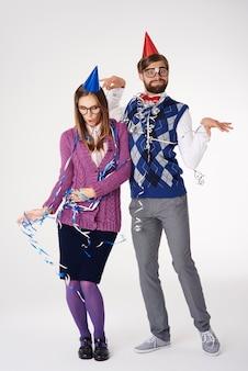 Pareja nerd con cintas y sombreros de fiesta