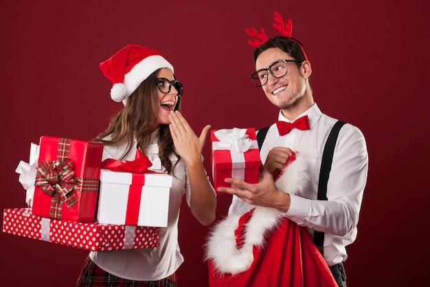 Pareja nerd intercambiando regalos de navidad