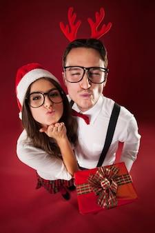 Pareja nerd soplando besos en navidad