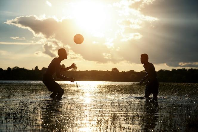 Pareja niño jugando fútbol con fondo puesta de sol