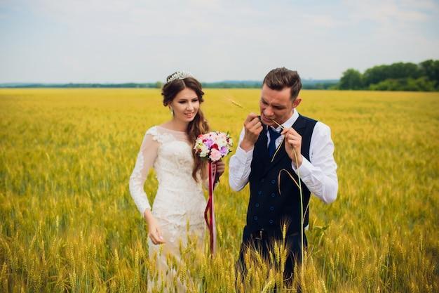 Pareja novia y el novio en el fondo del campo.
