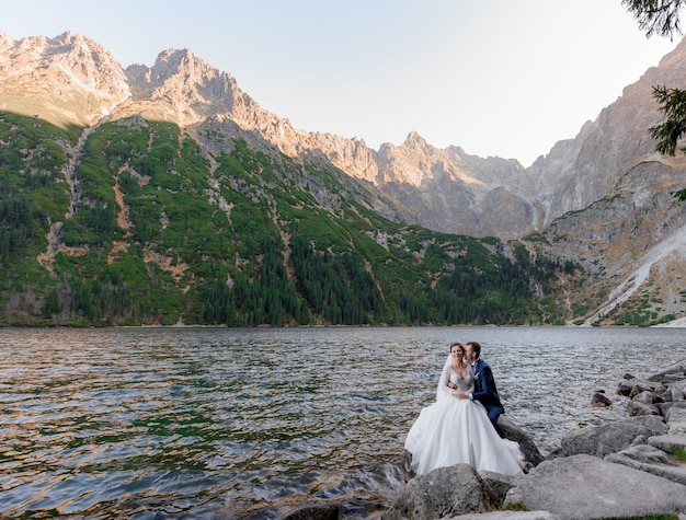 Pareja de novios se besa cerca del lago en las montañas de otoño, morskie oko