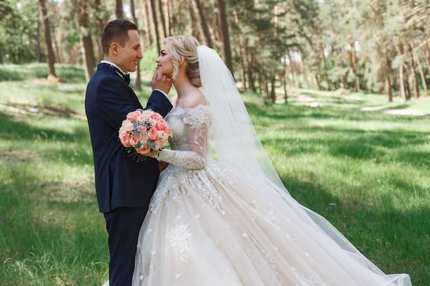 Pareja de novios emocional sobre la hierba verde en la primavera. amor de dos personas. novios abrazos y besos suaves en el día de la boda en la naturaleza. retrato de hermosos recién casados al aire libre. concepto de la boda