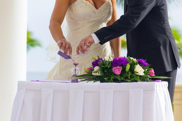 Pareja de novios practica ceremonia de mezcla de arenas con ramo de flores en la mesa