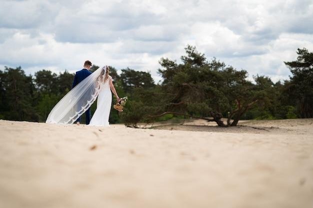 Pareja de novios recién casados camina a un lugar de picnic para disfrutar de la vida y celebrar con una botella de vino