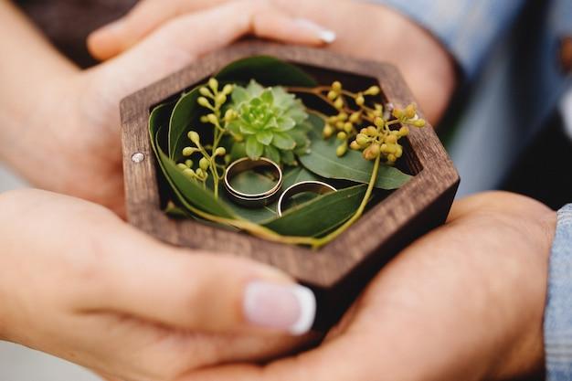 Pareja de novios está sosteniendo sus anillos de boda. foto de alta calidad