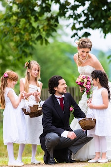 Pareja nupcial en la boda con los niños de la dama de honor