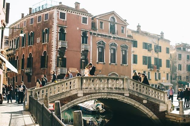 Pareja nupcial romántica en un puente en venecia