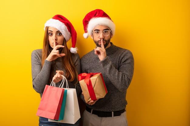Pareja o amigos que tienen regalos y bolsas de compras guardando un secreto o pidiendo silencio