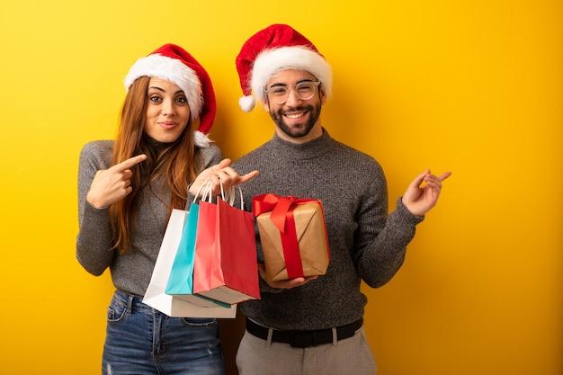 Pareja o amigos sosteniendo regalos y bolsas de compras sosteniendo algo con la mano