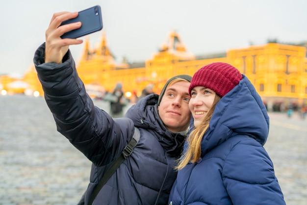 Pareja o hombre y mujer tomando un autorretrato al aire libre en la calle en un día de invierno