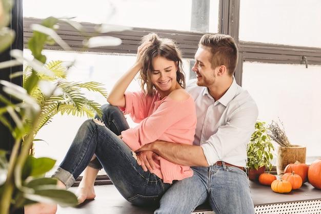 Pareja o matrimonio en su nueva casa mirando por la ventana