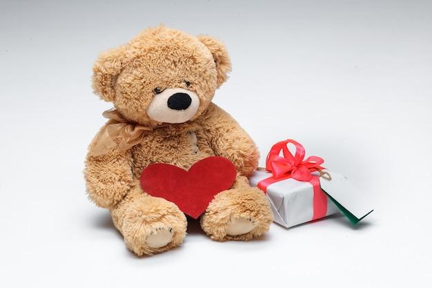 Pareja de osos de peluche con corazón rojo y regalo sobre fondo blanco. concepto de día de san valentín.