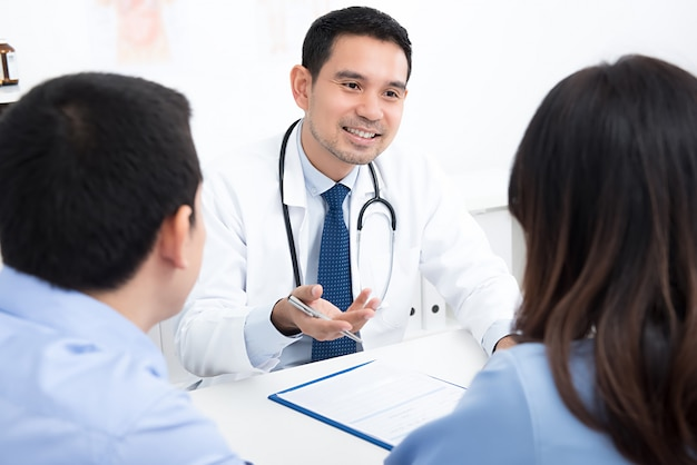 Pareja de pacientes que consultan con el médico.