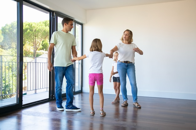 Pareja de padres y dos niños disfrutando de su nuevo hogar, de pie en una habitación vacía y tomados de la mano, bailando