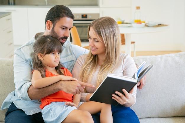 Pareja de padres felices y niña de pelo negro sentada en el sofá en la sala de estar y leyendo un libro juntos.