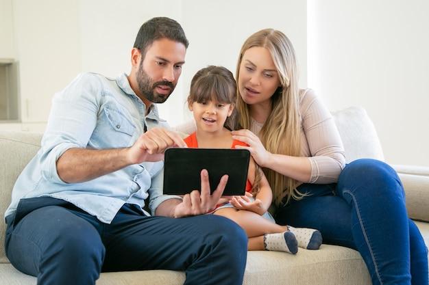 Pareja de padres jóvenes y linda hija sentada en el sofá, usando tableta para videollamadas o ver películas.