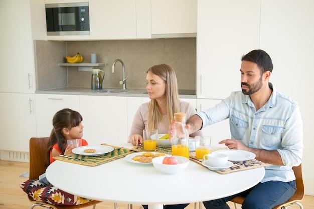 Pareja de padres y una niña desayunando, sentados en la mesa de comedor con frutas, galletas y jugo de naranja, hablando y comiendo.