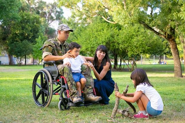 Pareja de padres pensativos y pacíficos que pasan tiempo libre con los niños al aire libre, preparando leña para fuego en el césped veterano discapacitado o concepto de familia al aire libre