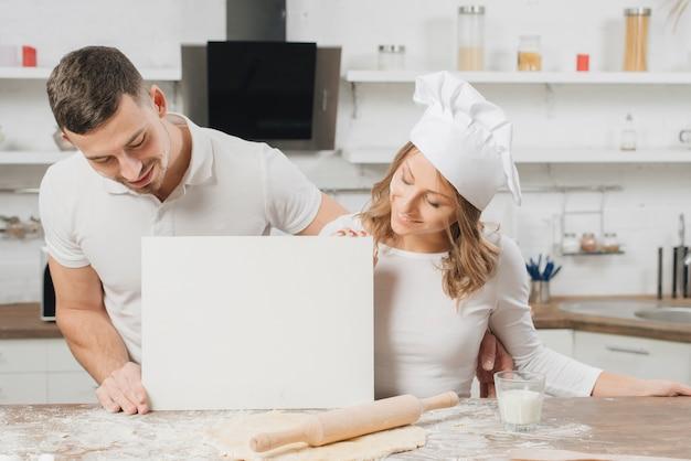 Pareja con papel en blanco en cocina