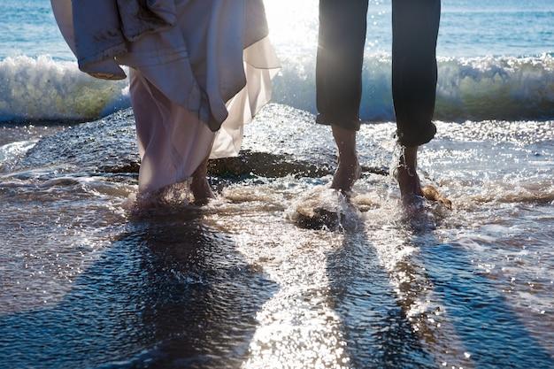 Pareja de pareja heterosexual divirtiéndose salpicando olas en la playa.