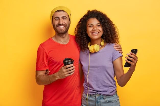 La pareja pasa tiempo libre juntos, bebe café y usa los teléfonos celulares modernos para la comunicación en línea, vestidos con camisetas, de pie cerca uno del otro contra el fondo amarillo